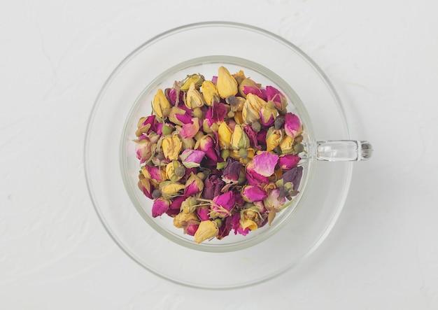 バラのつぼみは、白い背景の上の透明なガラスのカップにお茶を混ぜます。上面図