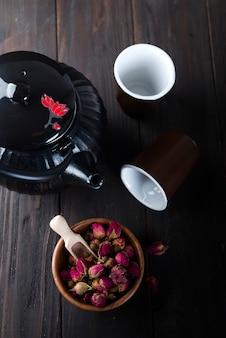 Розовый бутон чай на деревянной миске с чайником