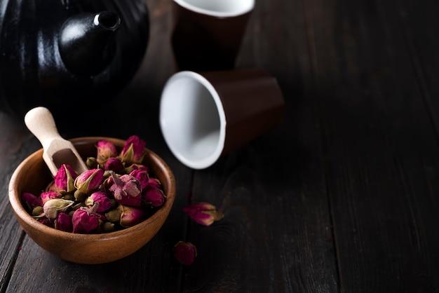 ティーポットで木製のボウルにローズバッド茶