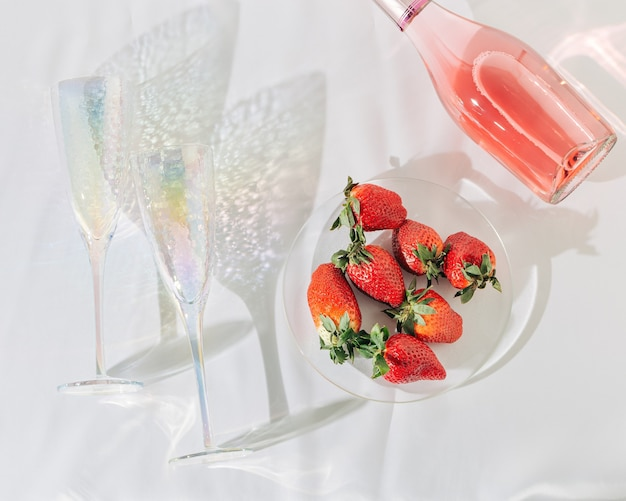 Rose champagne in bottle bright glasses for wine and and strawberry on white silk surface