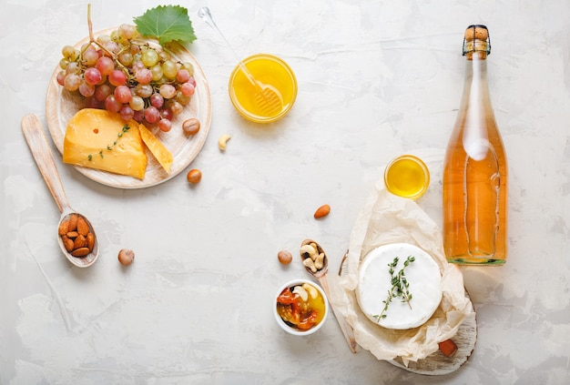 Rose champagne pink wine or apple cider bottle with appetizer set cheese grapes honey nuts on light gray stone background. festive table served with wine and snacks food drinks.