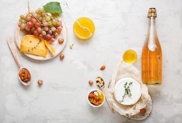 연한 회색 돌 배경에 전채 세트 치즈 포도 꿀 견과류와 함께 로즈 샴페인 핑크 와인 또는 사과 사이다 병. 와인과 스낵 음식 음료와 함께 제공되는 축제 테이블.