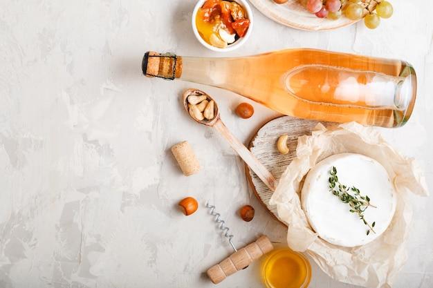 연한 회색 돌 배경에 전채 세트 치즈 포도 꿀 견과류와 함께 로즈 샴페인 핑크 와인 또는 사과 사이다 병. 와인 파티 낭만적인 저녁 식사를 위한 지중해 음식 음료.