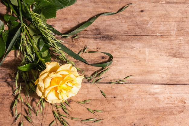 Rose decorative background. fresh yellow flower, hard light, dark shadow. vintage wooden boards background, place for text