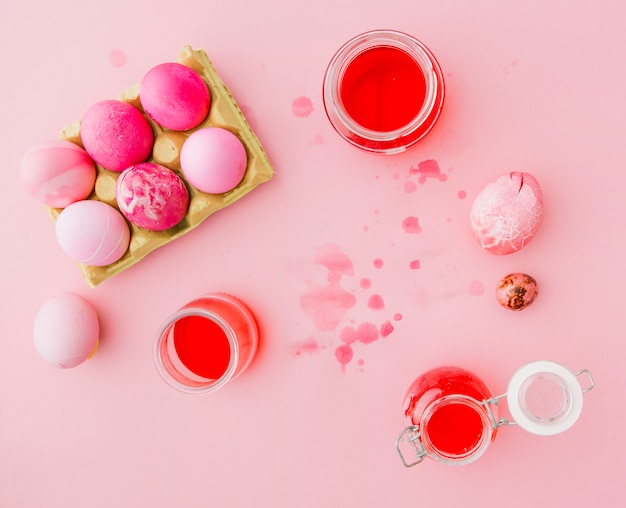 Rose easter eggs near cans with dye liquid