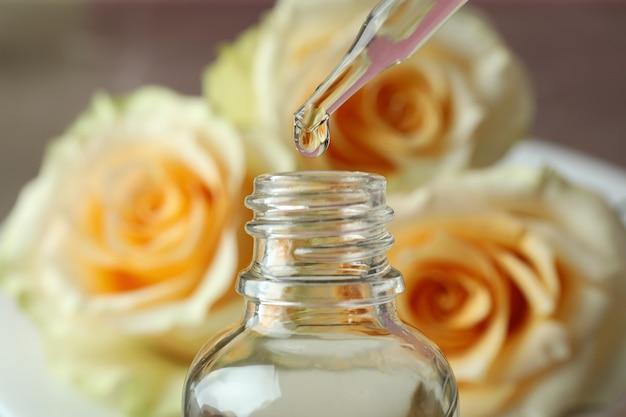 Эфирное масло розы падает из стеклянной капельницы в бутылку