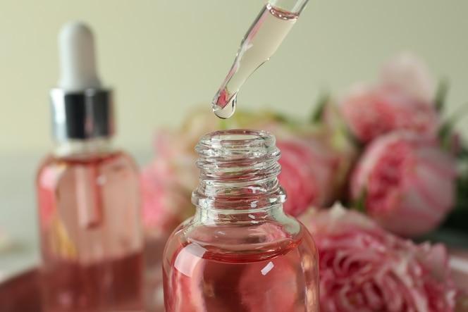 olio essenziale di rosa che cade dal contagocce di vetro in una bottiglia