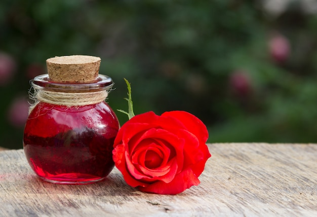 Rose essential oil in a round bottle and red rose