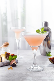 The rose exotic cocktail and figs, honey on light background over windows, copy space