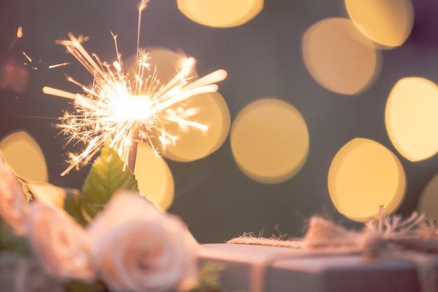 Цветок розы, подарочная коробка, бенгальский огонь, на деревянном столе с боке