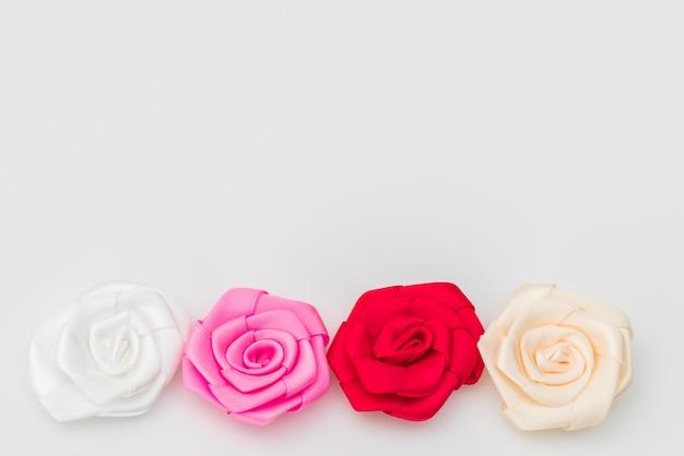 白い背景の上にリボンの花ローズ。