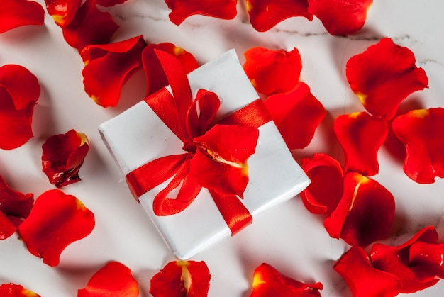 Rose flower petals and white wrapped gift box with red ribbon on white marble background