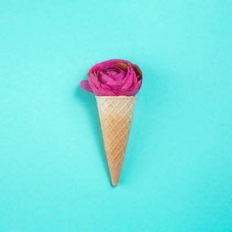 Rose flower in waffle cone on table