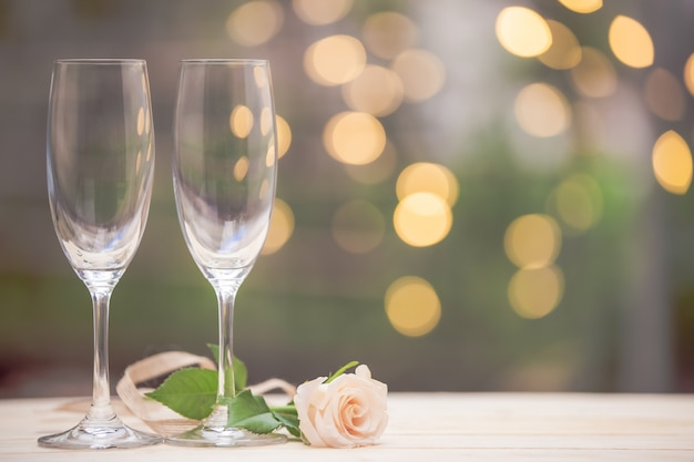 Rose flower with glass wine on wooden table blur bokeh