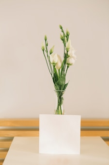 Rose flowers in vase with blank paper
