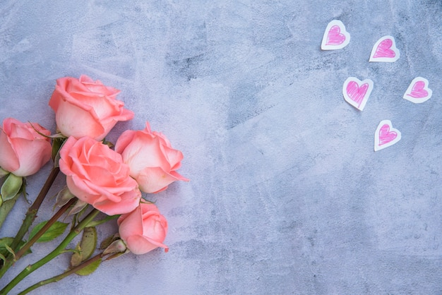 Rose flowers with paper hearts on table