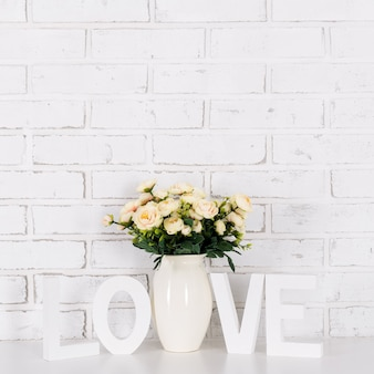 Rose flowers and wooden letters love over white brick wall