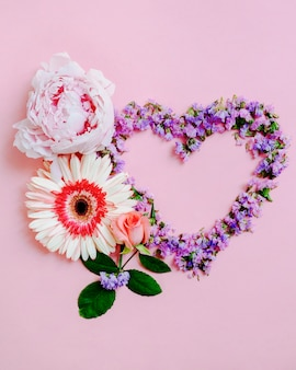 Rose, gerbera and peony flower with heart shape on pink background