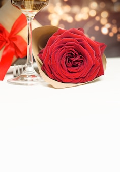 Rose, glass of champagne and a gift on a white table with copy space