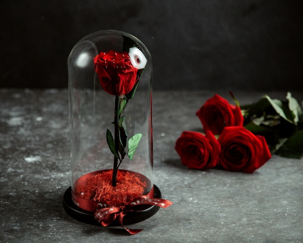 Rose in glass dome and red roses on table