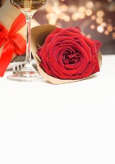 Роза, бокал шампанского и подарок на белом столе с копией пространства