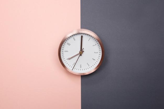 파스텔 핑크와 회색 배경에 로즈 골드 시계. 최소한의 아이디어 사업 개념입니다.