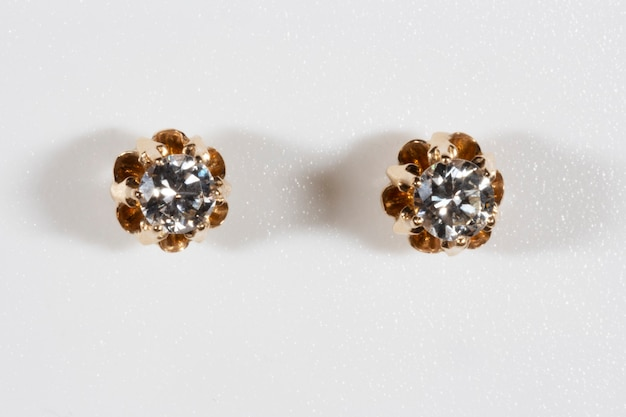 Rose gold diamond solitaire earrings on a white