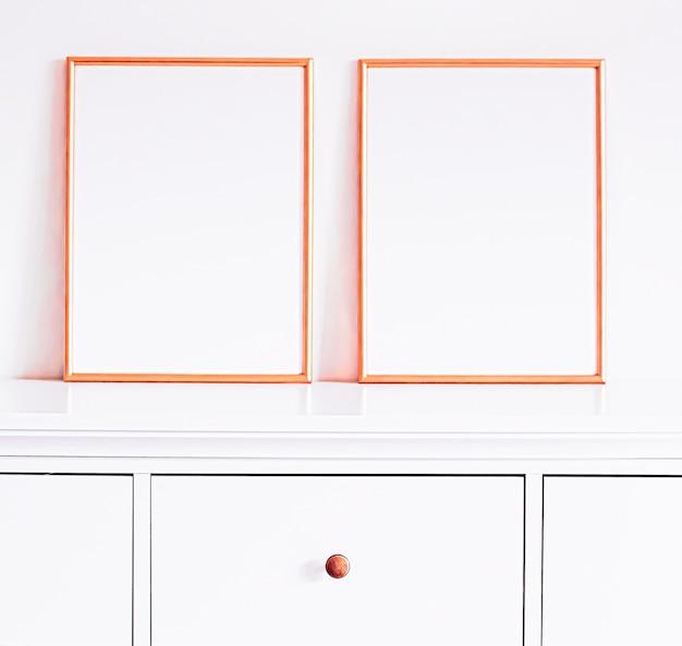 モックアップポスタープリントと印刷可能なアートオンラインショップショーケースのための白い家具の豪華な家の装飾とデザインのローズゴールドフレーム