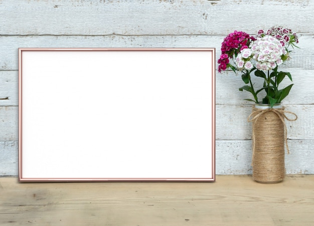 Rose gold horizontal frame near a bouquet of sweet-william stands on a wooden table 3d render