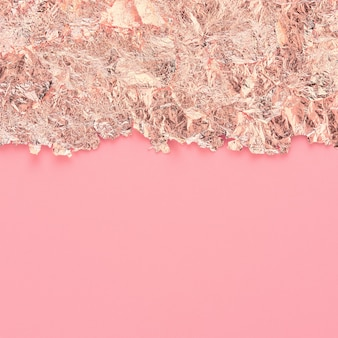 Rose gold paper torn edge border, pink abstract background, copy space.