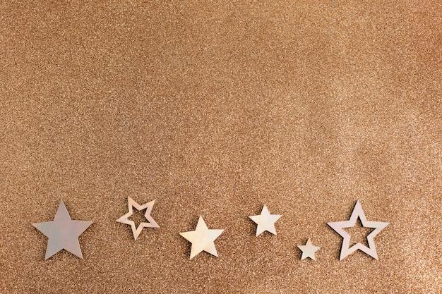 ローズゴールドの星とキラキラの明るい茶色の背景。ホリデーパーティーの装飾。