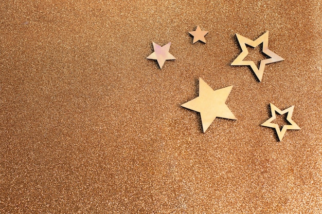 Rose gold stars and glitter on light brown background. holiday party decoration. new year celebration.