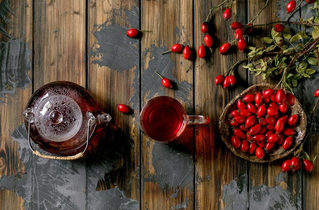 Rose hip berries herbal tea in glass teapot and cup standing on old wooden plank background with wild autumn berries around. winter hot beverage. flat lay, copy space