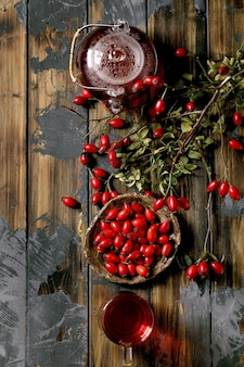 Rose hip berries herbal tea in glass teapot and cup standing on old wooden plank background with wild autumn berries around. winter hot beverage. flat lay