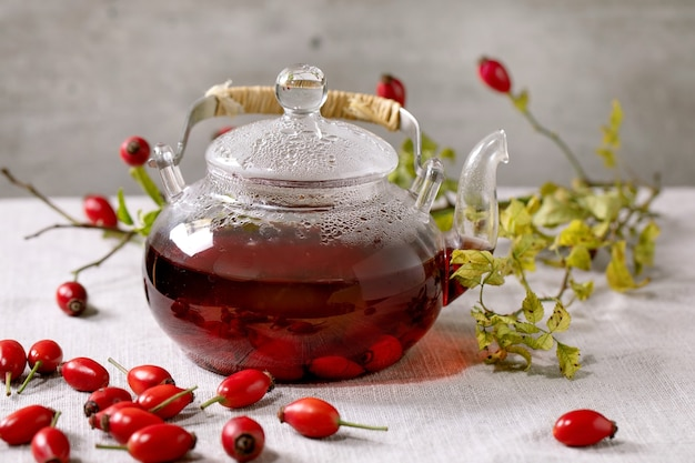 Rose hip berries herbal tea in glass teapot standing on white linen table cloth with wild autumn berries around. healthy hot drink.