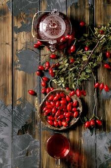 Травяной чай ягод шиповника в стеклянном чайнике и чашке, стоящей на старой деревянной предпосылке доски с дикими ягодами осени вокруг. зимний горячий напиток. плоская планировка