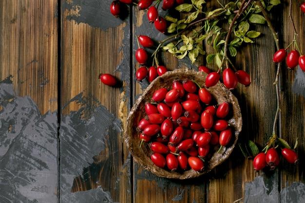 Ягоды шиповника на керамической тарелке с ветвью и листьями на старой деревянной предпосылке планки. осенние запасы витаминов на зиму. плоская планировка, копия пространства