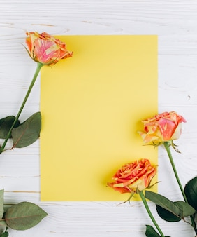 Rose in yellow and red colors with clean sheet of paper on a white wooden background.