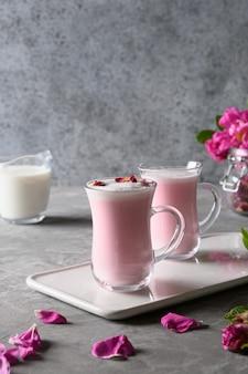 유리 컵에 장미 달 우유와 회색 배경에 떨어지는 장미 꽃잎. 확대. 수직 형식.