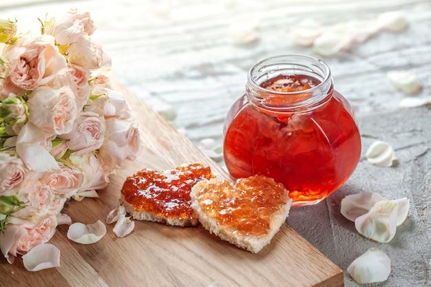 Варенье из лепестков розы и бутерброд в форме сердца с мармеладом розовым цветком на столе.