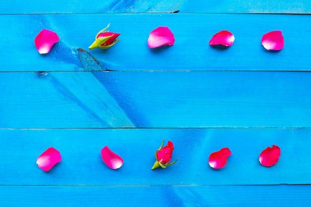 Rose petals on blue wooden background.