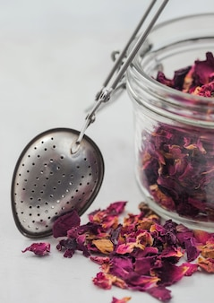 バラの花びらは、白い背景にヴィンテージストレーナー注入器とガラスの瓶にグレードのお茶を作ります。