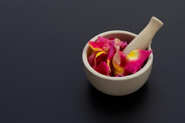 暗い表面に分離された乳棒と乳鉢のバラの花びら。