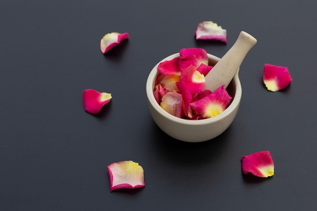 Rose petals in porcelain mortar with pestle isolated on dark surface.