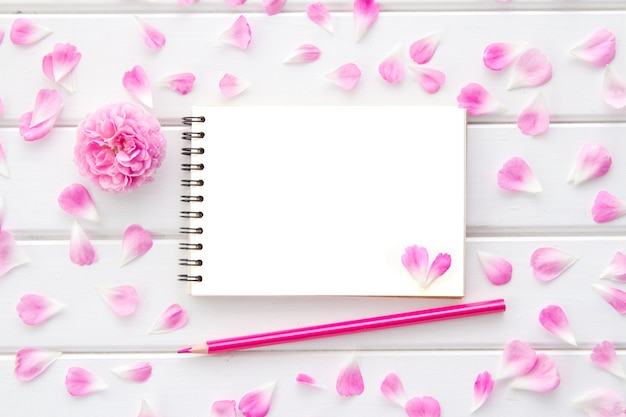 Rose petals and a rose, an empty notepad and a pink pencil on a white wood, flat lay