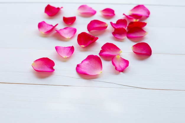 Rose petals on white wooden background.