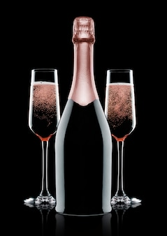 Rose pink champagne glasses and bottle on black background with reflection
