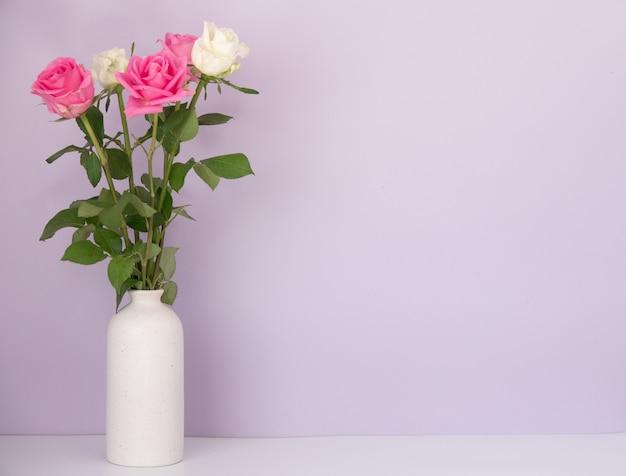 青い表面の机の上に置かれたバラ