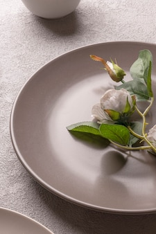 Rose in a plate on the table, gray pastel colors. romantic minimalistic lifestyle still life. vertical photo for a love story.