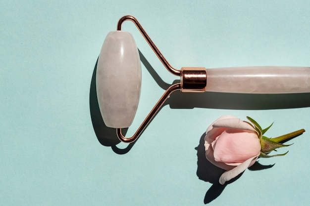 Rose quartz jade roller on blue background. anti age, lifting and toning treatment massaging at home. copy space.